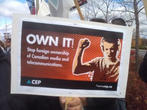 CEP sign reading: OWN IT! Stop foreign ownership of Canadian media and telecommunications. CEP www.cep.ca